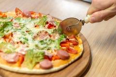 厨师面包师的特写镜头手切比萨的白色制服的在厨房,软的选择聚焦 免版税库存图片