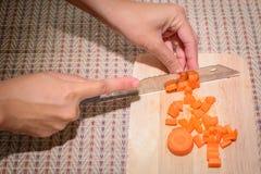 厨师面对一棵大红萝卜 免版税库存照片