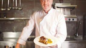 厨师,厨师画象拿着盘用沙拉,准备好饭食显示,看照相机,微笑的厨师以厨师` s形式  股票录像