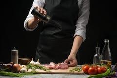 厨师,烹调牛排肉在厨房里,洒在菜背景的盐,蕃茄、辣子、蓬蒿和迷迭香 T 免版税库存图片