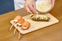 厨师洒与乳酪被充塞的茄子 免版税图库摄影