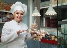 年轻厨师画象糖果店显示的用酥皮点心 库存图片