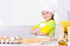 厨师` s帽子烘烤蛋糕的逗人喜爱的小女孩在厨房里 图库摄影