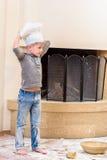 厨师` s帽子的一个男孩在壁炉附近坐厨房地板弄脏用面粉,使用用食物,做混乱 免版税图库摄影