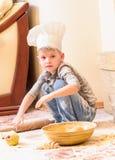 厨师` s帽子的一个男孩在壁炉附近坐厨房地板弄脏用面粉,使用用食物,做混乱 免版税库存照片