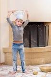 厨师` s帽子的一个男孩在壁炉附近坐厨房地板弄脏用面粉,使用用食物,做混乱 库存照片