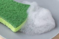 厨房与泡沫洗涤剂的绿色海绵在一块灰色板材 图库摄影
