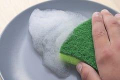 厨房与泡沫洗涤剂的绿色海绵在一块灰色板材 免版税库存图片