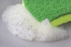 厨房与泡沫洗涤剂的绿色海绵在一块灰色板材 库存照片