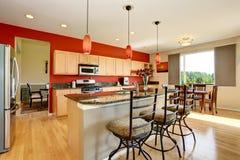 厨房与红色墙壁、花岗岩桌面和海岛的室内部 库存图片