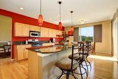 厨房与红色墙壁、花岗岩桌面和海岛的室内部 免版税库存图片