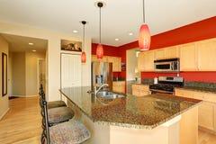 厨房与红色墙壁、花岗岩桌面和海岛的室内部 免版税图库摄影