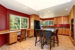 厨房与红色墙壁的室内部,花岗岩桌面和酒吧站立 库存照片