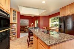 厨房与红色墙壁的室内部,花岗岩桌面和酒吧站立 库存图片