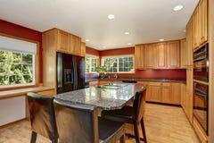 厨房与红色墙壁的室内部,花岗岩桌面和酒吧站立 免版税图库摄影