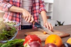 厨房健康生活方式身分藏品刀子切口红萝卜特写镜头的少女 免版税库存照片
