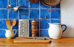 厨房内部静物画 葡萄酒器物陶瓷投手、切板、刀子、木匙子,胡椒和金属 免版税库存照片