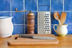 厨房内部静物画 葡萄酒器物陶瓷投手、切板、刀子、木匙子,胡椒和金属 免版税库存图片