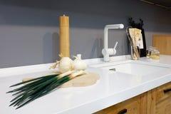 厨房内部,有五谷的玻璃瓶子在有白色搅拌器的,葱,大蒜,香料,木砧板现代厨房里;w 免版税图库摄影