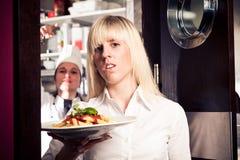从厨房出来的被注重的侍者 免版税库存照片