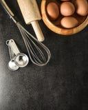 厨房器物和烘烤成份:鸡蛋和面粉在黑背景 免版税库存照片