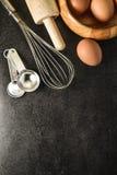 厨房器物和烘烤成份:鸡蛋和面粉在黑背景 免版税库存图片