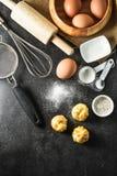 厨房器物和烘烤成份:鸡蛋和面粉在黑背景 免版税图库摄影