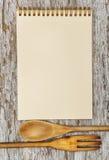 厨房器物和纸螺纹笔记本在老木头 免版税图库摄影
