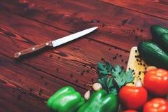 厨房工作场所概念 新鲜蔬菜、香料和刀子在木桌上 库存照片
