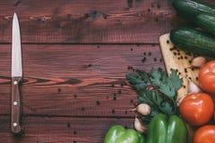 厨房工作场所概念 新鲜蔬菜、香料和刀子在木桌上 免版税图库摄影