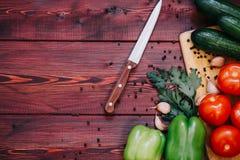 厨房工作场所概念 新鲜蔬菜、香料和刀子在木桌上 免版税库存图片