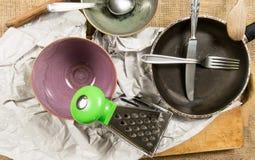 厨房工具-两个碗、叉子、刀子、木匙子、平底锅、磨丝器和纸 免版税库存照片