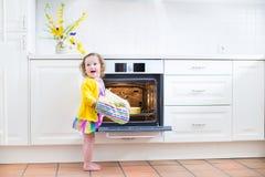 厨房手套的小孩女孩在与苹果饼的烤箱旁边 免版税图库摄影