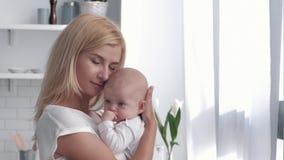 厨房的新的母亲在家拥抱和亲吻女婴,幸福家庭画象  影视素材