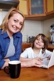 厨房膝上型计算机母亲坐儿子使用 库存图片