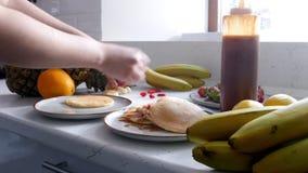 厨房-妇女在薄煎饼放置香蕉并且倒浓缩牛奶 股票视频