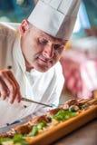 主厨 厨师烹调 装饰盘的厨师 准备膳食的厨师 厨师在旅馆或餐馆厨房准备装饰盘与 免版税库存照片