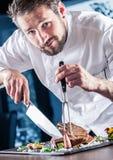 主厨 有刀子和叉子的厨师 专业厨师在餐馆或旅馆准备或切开丁骨牛排 准备牛排的厨师 免版税库存图片