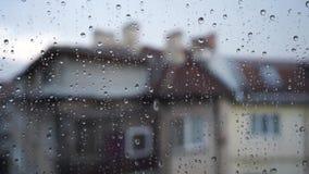 去下来在窗玻璃的下落 水滴特写镜头在玻璃的 与迷离大厦的雨在背景中 r 影视素材