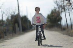 去与她的往照相机微笑的自行车的小女孩 库存图片