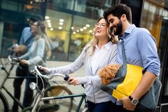 去为自行车乘驾的微笑的年轻夫妇在一好日子在城市 免版税库存照片