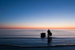 去他的小船的渔夫在surise的海 图库摄影