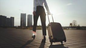 去企业的夫人乘出租车从机场的停车处有她的行李的 脚跟跨步和卷手提箱的女孩  股票视频