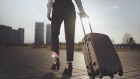 去企业的夫人乘出租车从机场的停车处有她的行李的 脚跟跨步和卷手提箱的女孩  股票录像