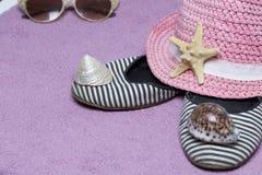 去休假在海滩 保护免受太阳和一个对的帽子太阳镜 海滩运动鞋和海星 反对 库存图片
