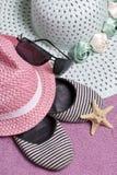 去休假在海滩 保护免受太阳和一个对的帽子太阳镜 海滩运动鞋和海星 反对 免版税库存图片