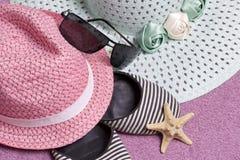 去休假在海滩 保护免受太阳和一个对的帽子太阳镜 海滩运动鞋和海星 反对 免版税库存照片