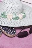 去休假在海滩 保护免受太阳和一个对的帽子太阳镜 海滩运动鞋 反对背景o 免版税库存图片