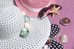 去休假在海滩 保护免受太阳和一个对的帽子太阳镜 海滩运动鞋 海星和贝壳 库存图片
