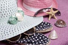 去休假在海滩 保护免受太阳和一个对的帽子太阳镜 海滩运动鞋 海星和贝壳 库存照片
